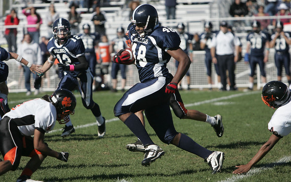 North Shore Tech's Jordan Smith runs the ball down the field while being defended by Greater Lawrence Tech during the Saturday afternoon game held at North Shore Tech in Middleton. Photo by deborah parker/october 9, 2010