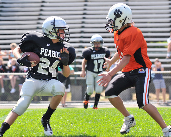 Beverly: Peabody Raiders Silver player Matt Schweizer carries the ball upfield facing a Beverly Black defenseman during a seventh and eighth grade northeast conference youth football game.  photo by Mark Teiwes / Salem News