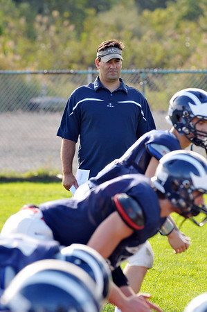 Swamscott: Swampscott High School varsity football head coach Steve Dembowski watches as his team runs drills during practice.  photo by Mark Teiwes / Salem News