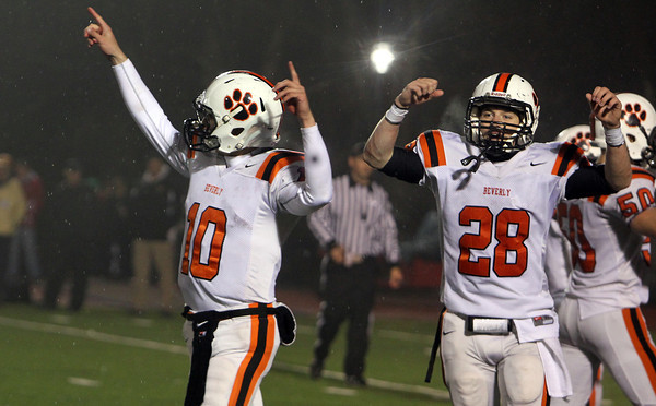 Beverly senior captains Dave Rollins, left, and Kenny Pierce walk off Varsity Field in Burlington with their arms raised high after the Panthers defeated the Red Devils 34-21 to advance to the D2A Super Bowl for the 2nd time in 3 years. David Le/Staff Photo