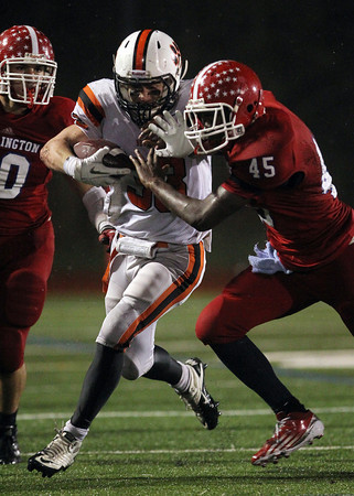 Beverly senior running back Brendan Flaherty stiff-arms Burlington senior Marcus Aaron Odiah, right, out of the way during the 4th quarter of play on Tuesday evening in the Eastern Mass D2A semi-final. David Le/Staff Photo