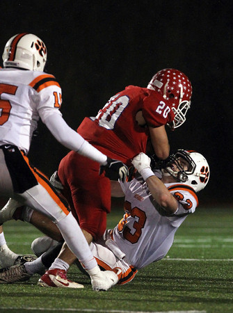 Beverly senior captain Brendan Flaherty, drags down Burlington running back Christopher Arria in the 2nd quarter of play on Tuesday night. David Le/Staff Photo