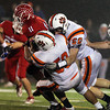 Beverly High School juniors Sean Winston, center, and Zach Duguid, right, bring down Burlington running back Anthony Cruz, left, down during the second quarter of play on Tuesday evening. David Le/Staff Photo