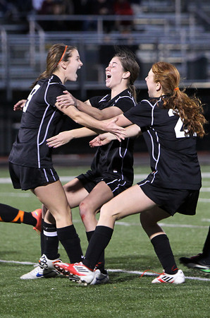 Beverly junior Caitlin Harty, center, and sophomore Rose Terner, right, mob junior captain Diandra Crowley, left, after she buried the winninng penalty kick for the Panthers, sending Beverly home with their first D1 North Title in school history. David Le/Staff Photo