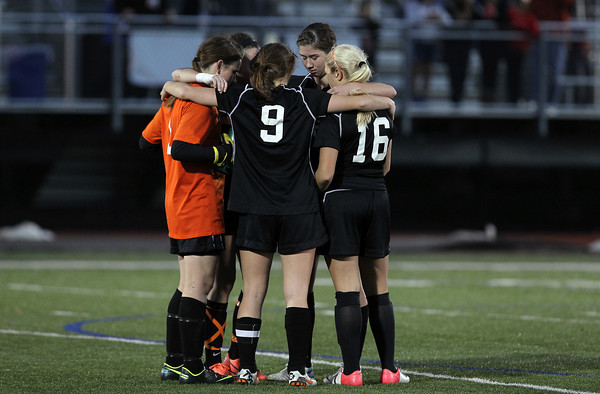Beverly High School junior goalie Casey Cook, left, and penalty takers Diandra Crowley, Eva Gourdeau, Caitlin Harty, and Kristen O'Connor gather in a small huddle before the start of the penalty kick rounds against Central Catholic on Sunday afternoon. The Panthers buried their first 4 shots and defeated the Raiders 4-1 on PK's to capture the school's first Girls Soccer D1 North Title. David Le/Staff Photo