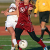 Beverly senior midfielder Allison Collins, left, reaches around Concord-Carlisle junior midfielder Allie Barrett, right, to poke the ball away during the second half of play on Tuesday afternoon. Behind 2 goals from junior Caitlin Harty, the Panthers advanced to the D1 North Semi-Final, defeating CC 2-0. David Le/Staff Photo