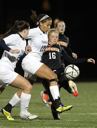 Beverly sophomore Eva Goudreau, right, makes a sliding challenge on Franklin sophomore Lexi Martin, left, and manages to kick the ball away in the first half of play in the D1 State Semi-Final at Manning Field in Lynn. David Le/Staff Photo