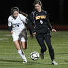 Beverly junior striker Caitlin Harty, right, turns upfield with the ball while being pursued by Franklin junior Julia Bireley, left, on Wednesday evening in the first half of the D1 State Semi-Final match at Manning Field in Lynn. David Le/Staff Photo