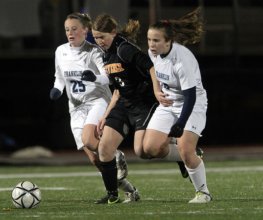 Beverly junior midfielder Casey Cook, center, splits two Franklin defenders on Wednesday evening in the D1 State Semi-Final at Manning Field in Lynn. David Le/Staff Photo