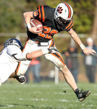Beverly senior running back Kenny Pierce right, leaps in the air, but can't avoid diving Marblehead cornerback Zac Cuzner, left, on Saturday afternoon. David Le/Staff Photo