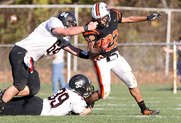 Marblehead junior Trevor Gelineau, left, gets a grasp of Beverly running back Isiah White's facemask, right, while Magician teammate junior Ben Anderson, center, grabs ahold of his legs. The 8-1 Magicians and 9-0 Panthers clashed on Saturday afternoon for the NEC/CAL Tier 2 Championship. Beverly defeated Marblehead 35-14 in front of a large home crowd at Hurd Stadium. David Le/Staff Photo