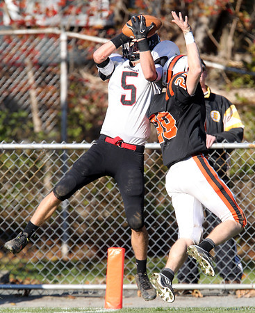 Marblehead junior wide receiver Dylan Cressy, left, leaps over Beverly cornerback Kenny Pierce, right, to haul in a touchdown from Magicians quarterback Ian Maag on Saturday afternoon. However, Beverly defeated Marblehead to move to a perfect 10-0 and captured the NEC/CAL Tier 2 Championship. David Le/Staff Photo