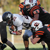Marblehead running back Zac Cuzner, left, gets brought down by Beverly senior Dom Abate, right, and junior Sean Winston, center, on Saturday afternoon. David Le/Staff Photo