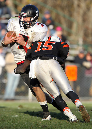 Marblehead senior quarterback Ian Maag can't avoid the tackle of Beverly junior linebacker Sam Mulumba and is dragged down for only a short gain in the 4th quarter of Saturday's contest between the two top teams in the NEC/CAL. Beverly defeated Marblehead 35-14 to take home the NEC/CAL Tier 2 Championship at Hurd Stadium. David Le/Staff Photo