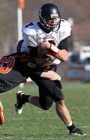 Marblehead senior quarterback Ian Maag covers the ball as he gets hit by Beverly safety Brendan Flaherty, left, during the first quarter of play. David Le/Staff Photo