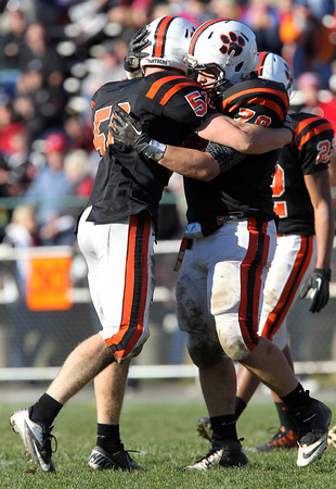 Beverly junior Zach Duguid, left, and senior Mike Dooling, right, celebrate after Duguid brought down Marblehead running back Brooks Tyrrell for a loss in the third quarter of play on Saturday afternoon. David Le/Staff Photo