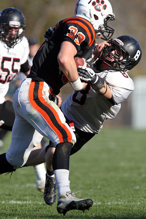 Marblehead senior Sam Stern, right, gets stiffarmed by Beverly senior running back Brendan Flaherty, left, during the first half of play on Saturday afternoon. David Le/Staff Photo
