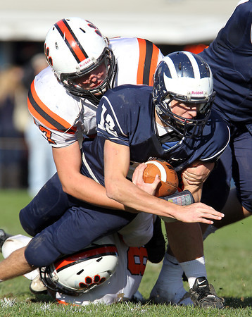 Beverly senior captain Marc Babcock, left, brings down Swampscott senior captain Brian Santry on a QB scramble in the third quarter of play on Saturday afternoon. David Le/Staff Photo
