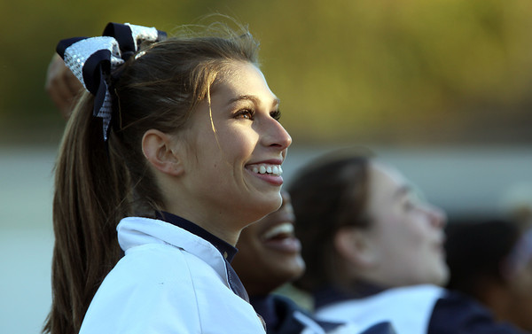 Swampscott junior cheerleader Elizabeth Kirby smiles up at the crowd after throwing foam footballs to spectators during the Big Blue football game on Saturday afternoon. David Le/Staff Photo