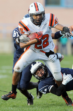 Beverly junior running back Isiah White, left, tries to break free from Swampscott's Brendan McDonald, right, on Saturday afternoon. David Le/Staff Photo