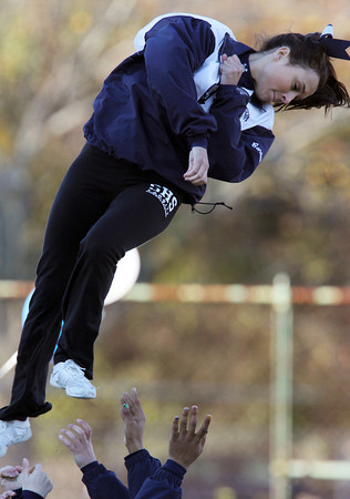 Swampscott senior cheerleader Candice O'Connor twists in midair as she is caught by her teammates during a stunt on Saturday afternoon at the Big Blue football game. David Le/Staff Photo