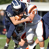 Swampscott senior captain Brian Santry, left, tries to break free from Beverly senior captain Marc Babcock, right, and senior Luke McDonald, center, on Saturday afternoon. The Panthers defeated the Big Blue 40-6 on Blocksidge Field. David Le/Staff Photo