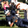 Swampscott junior wide receiver Aidan Brawley, left, holds onto the ball while being tackled by Beverly's Brendan Flaherty, right, on Saturday afternoon. David Le/Staff Photo