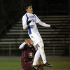 Danvers junior Caio Silva leaps high to win a head ball against a falling Concord-Carlisle defender on Tuesday evening. David Le/Staff Photo