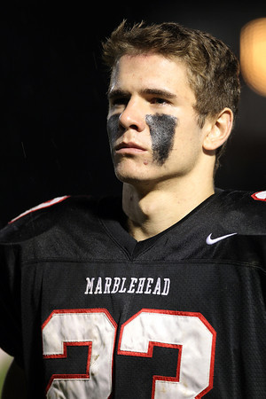 Marblehead junior Jeremy Gillis listens to the Marblehead High School Marching Band play the National Anthem prior to the start of their game against Danvers on Friday evening. David Le/Staff Photo