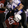 Danvers running back Alex Grant, right, tries to stay on his feet while being brought down by Salem's Austin Connolly, left, on Friday evening. David Le/Staff Photo