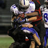 Danvers junior running back Alex Valles covers the ball while being brought down by two Salem defenders on Friday evening. David Le/Staff Photo
