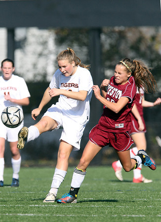 Ipswich High School junior Katie Monahan, left, boots the ball upfield while being pressured by Weston freshman Emma Marlow-Benedick, right, on Monday morning in the D3 North Final at Manning Field in Lynn. The Tigers fell to Weston 2-0. David Le/Staff Photo