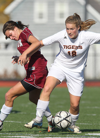 Ipswich High School junior Katie Monahan, right, controls the ball while getting tangled up with Weston senior Hannah Graves, left, on Monday morning. David Le/Staff Photo