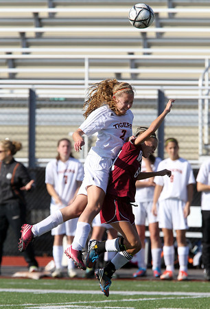 Ipswich High School junior Emily Evans, left, leaps high in the air to win a header over Weston freshman Emma Marlow-Benedick, right, on Monday morning. The Tigers fell to Weston 2-0 in the D3 North Final match at Manning Field in Lynn. David Le/Staff Photo
