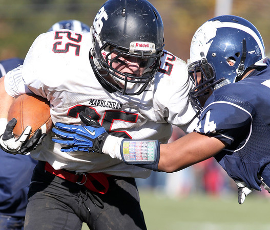 Marblehead running back Zac Cuzner, left, stiffarms Swampscott defender Michael Faia, right, on a run in the fourth quarter of play on Thursday morning. David Le/Staff Photo