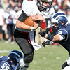 Marblehead quarterback Ian Maag tucks the ball away as he gets hit by two Swampscott defenders on Thursday morning during the annual Thanksgiving Day game. David Le/Staff Photo