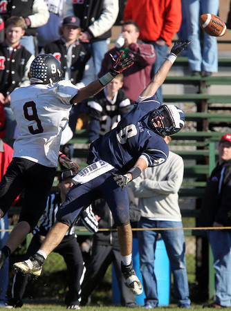Swampscott senior Aaron Cronin, right, leaps high but can't haul in a pass from Swampscott senior quarterback Brian Santry, while being defended by Marblehead sophomore Will Millett, left, on Thursday morning. David Le/Staff Photo