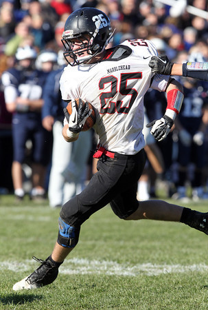 Marblehead senior running back Zac Cuzner shakes his way out of a tackle against Swampscott in the annual Thanksgiving Day game. David Le/Staff Photo