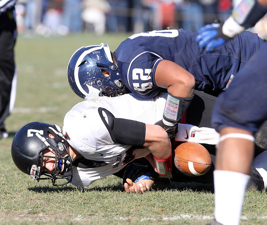 Swampscott's Joe Patsios, right, forces a fumble on Marblehead quarterback Ian Maag as he is brought to the ground on Thrusday morning. David Le/Staff Photo