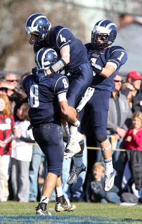 Swampscott senior Aaron Cronin, left, celebrates with teammates Ben Faulkner, center, and Corey Carmody, right, after Cronin scored a long touchdown from quarterback Brian Santry in the fourth quarter of play on Thursday morning. David Le/Staff Photo