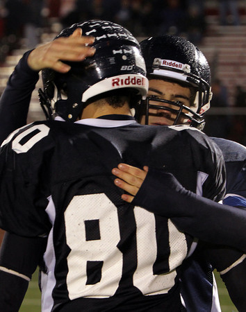 North Shore Tech junior RJ Conroy, right, gives senior Bryan Jackson a hug following a 30-14 loss to Cathedral in the Eastern Mass D4A semi-final on Tuesday evening at Varsity Field in Burlington. David Le/Staff Photo