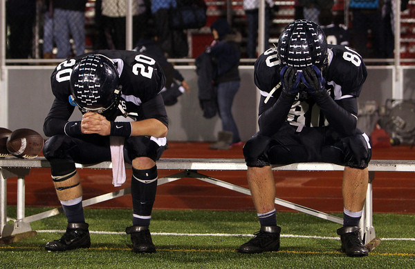 North Shore Tech seniors Tim Andersen, left, and Bryan Jackson, hold their heads in their hands after the Bulldogs fell to the Catedral Panthers 30-14 in the Eastern Mass D4A semi-final on Tuesday evening at Varsity Field in Burlington. David Le/Staff Photo