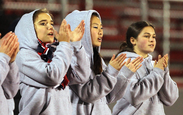 From left, North Shore Tech cheerleaders sophomore Ashley Eline, sophomore Kaleigh Stiratt, and freshman Jesse O'Neill, cheer on the Bulldogs as they squared off against Cathedral in the Eastern Mass D4A semi-final on Tuesday evening. David Le/Staff Photo