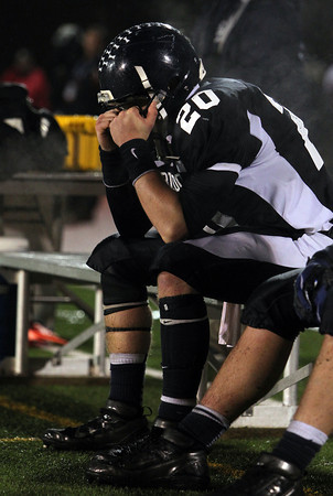 North Shore Tech senior quarterback Tim Andersen holds tightly onto his facemask and sits deep in thought following the Bulldogs' 30-14 loss to Cathedral on Tuesday evening in the Eastern Mass D4A semi-final game at Varsity Field in Burlington. David Le/Staff Photo