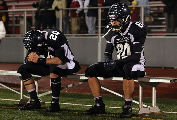 North Shore Tech seniors Tim Andersen, left, and Bryan Jackson, sit on the sidelines following a 30-14 defeat to the Cathedral Panthers on Tuesday evening in the Eastern Mass D4A semi-final. David Le/Staff Photo