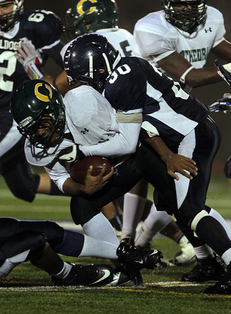 North Shore Tech junior Ian Lefavour, right, brings down Cathedral quarterback Kejonte Hickman on Tuesday evening in the Eastern Mass D4A semi-final. David Le/Staff Photo
