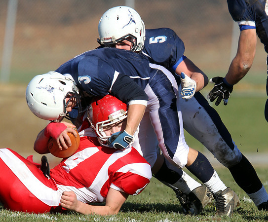 Peabody sophomore Ryan Collins, center, and junior Cody Wlasuk, right, make a stop on Saugus quarterback CJ Randolph, left, on Thanksgiving morning. David Le/Staff Photo