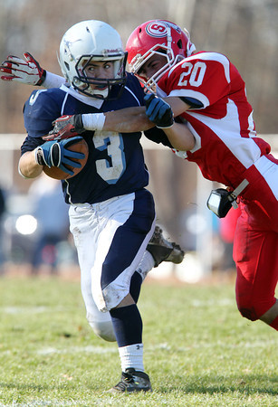 Peabody's Ryan Collins, left, gets tackled hard by Saugus defender Dan Cacciola, right, on Thanksgiving morning. David Le/Staff Photo
