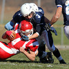 Saugus quarterback CJ Randolph, left, gets taken down by Peabody's Ryan Collins, right, on Thursday morning. David Le/Staff Photo