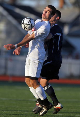 Masco senior captain Chip Sherman, left, controls the ball using his chest while being tightly contested by a St. John's Prep player in the first half of the D1 North Semi-Final match at Manning Field in Lynn. David Le/Staff Photo